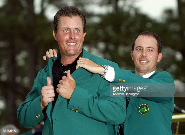 Masters winner Phil Mickelson of the U.S. Is presented the green jacket by 2003 Masters winner Mike Weir of Canada after the final round of the...