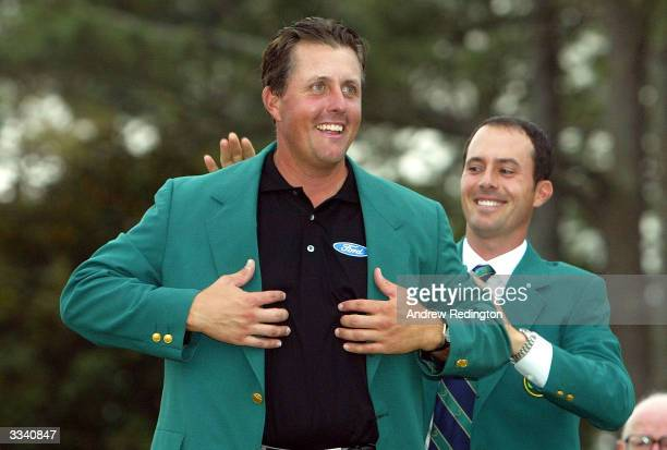 Masters winner Phil Mickelson of the USA is presented the green jacket by 2003 Masters winner Mike Weir of Canada after the final round of the...