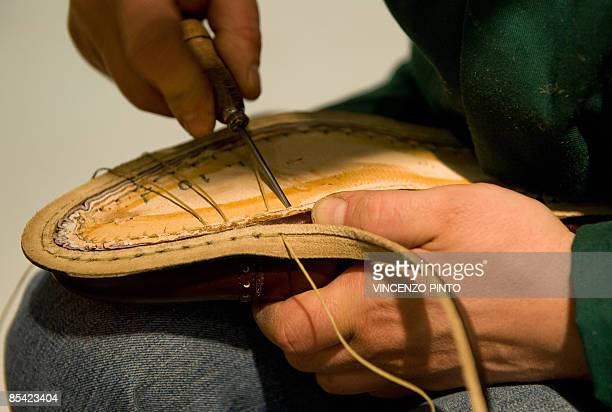 Mastro Lino, an employee in the famous luxurious shoes Italian manufactory De Tommaso, demonstrates a hand made sole of a shoe in the De Tommaso...