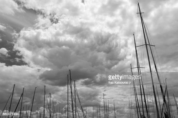Masts of sailing boats against cloudy sky