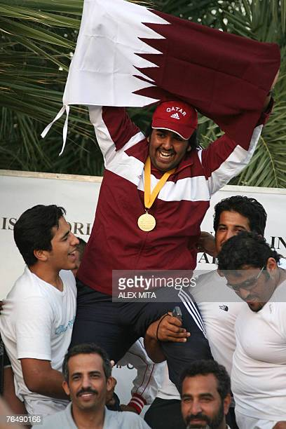 Masud alAbda celebrates with his team after winning the gold medal for the junior class double trap final competition during the first day of the...