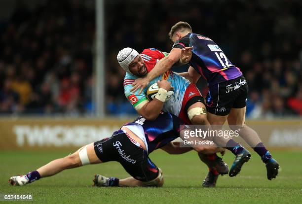 Mat Luamanu of Harlequins is tackled by Ollie Atkins and Sam Hill of Exeter during the AngloWelsh Cup Semi Final match between Exeter Chiefs and...
