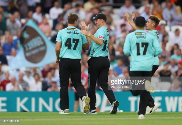Mat Pillans of Surrey is congratulated by team mate Rikki Clarke after dismssing Adam Wheater of Essex Eagles during the Vitality Blast match between...
