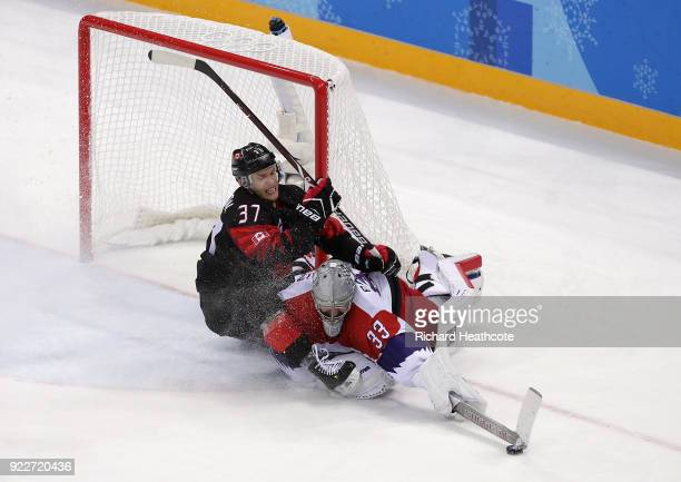 Mat Robinson of Canada collides with Pavel Francouz of the Czech Republic in overtime during the Men's Ice Hockey Preliminary Round Group A game on...