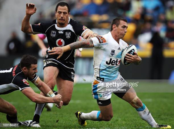 Mat Rogers of the Titans gets past Brett Seymour and Jesse Royal of the Warriors during the round 21 NRL match between the Warriors and the Gold...