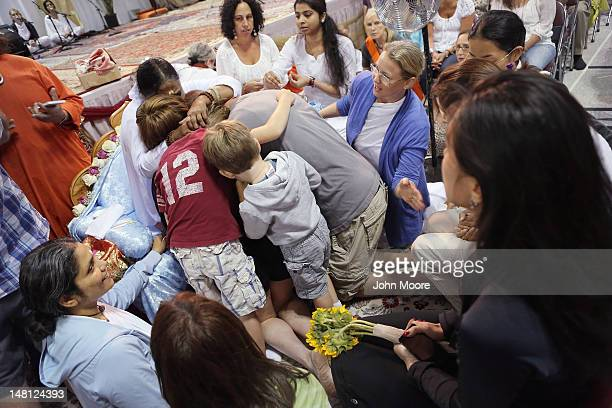 Mata Amritanandamayi also known as 'The Hugging Saint' embraces a family on July 10 2012 in New York City The Hindu spiritual leader and guru is on a...