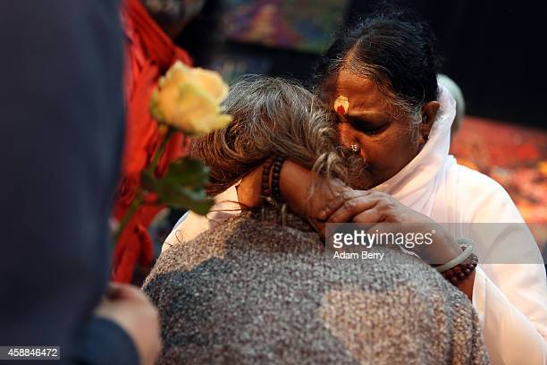 Mata Amritanandamayi Devi primarily known simply as Amma the hugging saint hugs a devotee as another brings her a flower in the event hall Arena on...