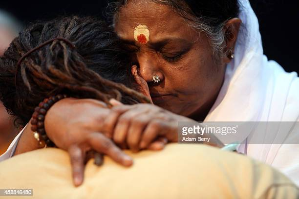 Mata Amritanandamayi Devi primarily known simply as Amma the hugging saint hugs a devotee in the event hall Arena on November 12 2014 in Berlin...