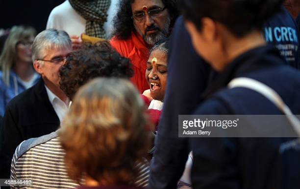 Mata Amritanandamayi Devi primarily known simply as Amma the hugging saint reacts to a child as she hugs devotees in the event hall Arena on November...
