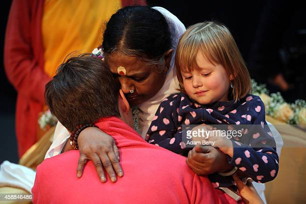 Mata Amritanandamayi Devi primarily known simply as Amma the hugging saint hugs a devotee and twoyearold Elena in the event hall Arena on November 12...