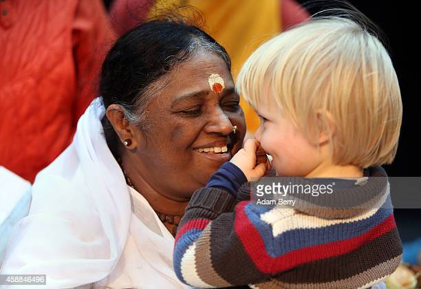 Mata Amritanandamayi Devi primarily known simply as Amma the hugging saint hugs a child in the event hall Arena on November 12 2014 in Berlin Germany...