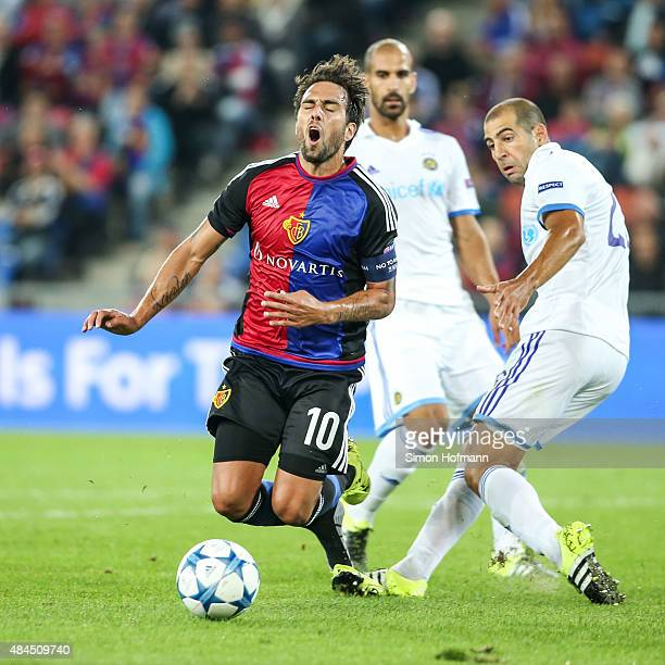 Matas Delgado of Basel is challenged by Tal Ben Haim of Tel Aviv during the UEFA Champions League qualifying round play off first leg match between...