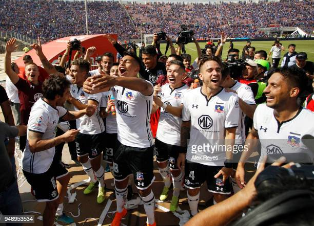 Matías Zaldivia and Ivan Morales of Colo Colo celebrate with teammates after winning the match between U de Chile and Colo Colo as part of Torneo...