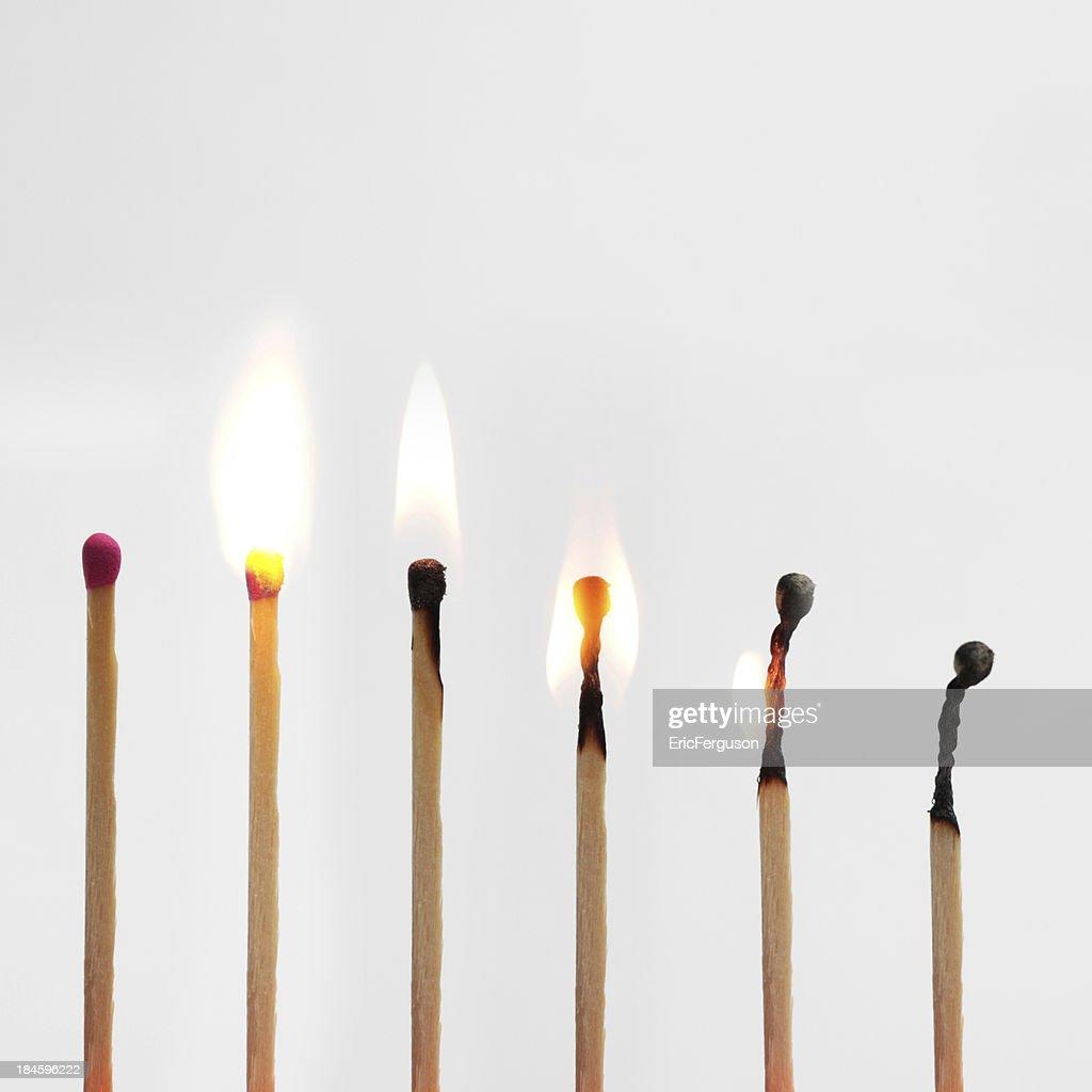Match burning down image progressionon grey : Stock Photo