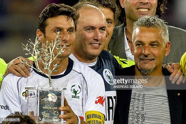 Match For Peace's Argentinian defender Javer Zanetti holds the trophy next to Abel Balbo and Roberto Baggio Match For Peace's players team at the end...