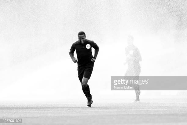 Match Official Akil Howson runs from the water sprinkler during the Sky Bet Championship match between Watford and Luton Town at Vicarage Road on...