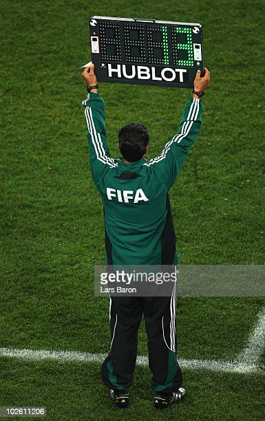 FIFA match official holds up an electronic board to signal a substitution during the 2010 FIFA World Cup South Africa Quarter Final match between...