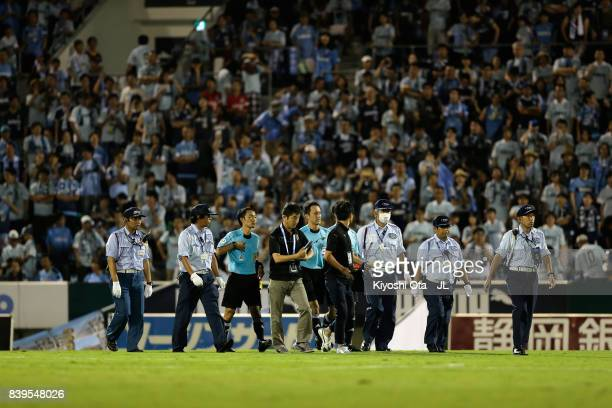 Match officials are protected by security staffs at the half time during the JLeague J1 match between Jubilo Iwata and Vissel Kobe at Yamaha Stadium...