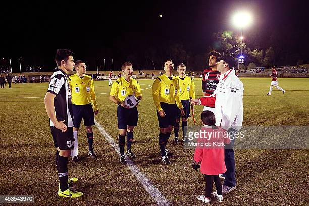 Match officials complete the coin toss before the FFA Cup match between Adelaide City and Western Sydney Wanderers at Marden Sports Complex on August...