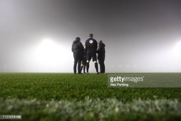 Match officials gather on the pitch as they make a decision to continue with the game during the Premier League 2 match between Arsenal and West Ham...