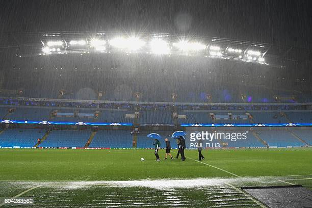 TOPSHOT Match officials inspect the pitch as heavy rain continues to pour ahead of the UEFA Champions League group C football match between...