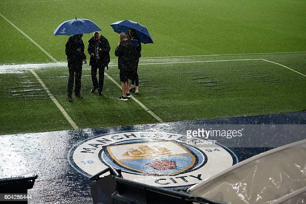 Match officials inspect the pitch as heavy rain continues to pour ahead of the UEFA Champions League group C football match between Manchester City...