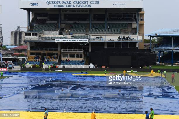 Match officials inspect the wet field as rain interrupt play of the first One Day International match between West Indies and India at the Queen's...