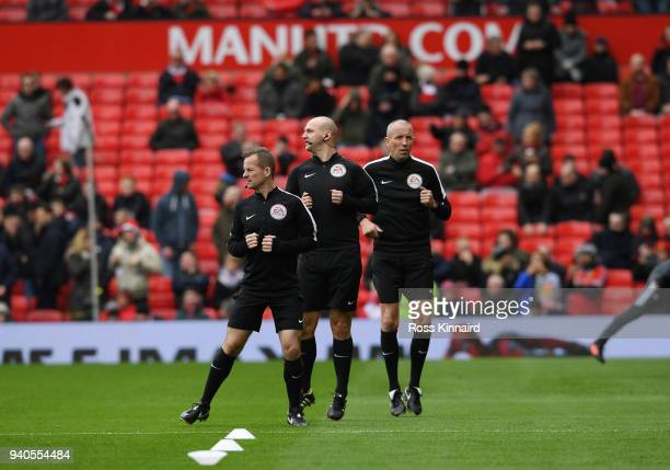 Match officials Marc Perry Bobby Madley and Mick McDonough warm up prior to the Premier League match between Manchester United and Swansea City at...