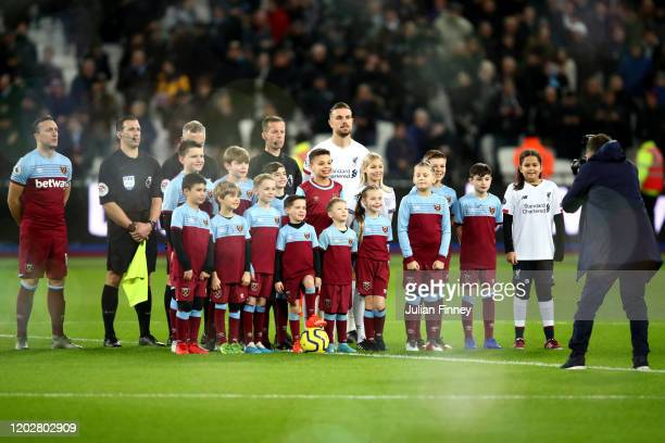 Match officials, players and mascots line up for a photo prior to the Premier League match between West Ham United and Liverpool FC at London Stadium...
