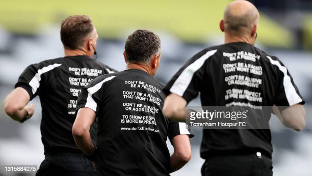 Match Officials, Scott Ledger, Andre Marriner and Simon Long warm up wearing t-shirt's that have writing detailing information about the 'don't x the...