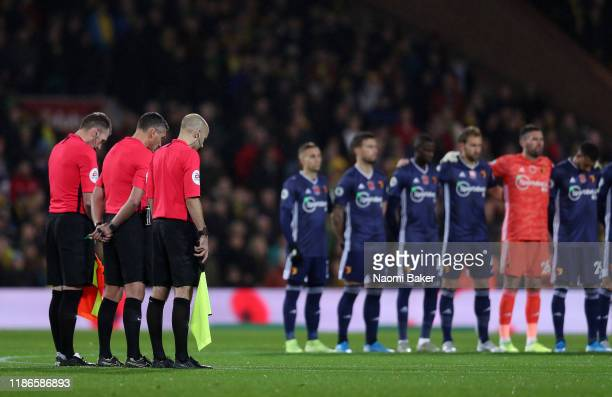Match officials stand for a minutes silence in honour of Remembrance Day during the Premier League match between Norwich City and Watford FC at...