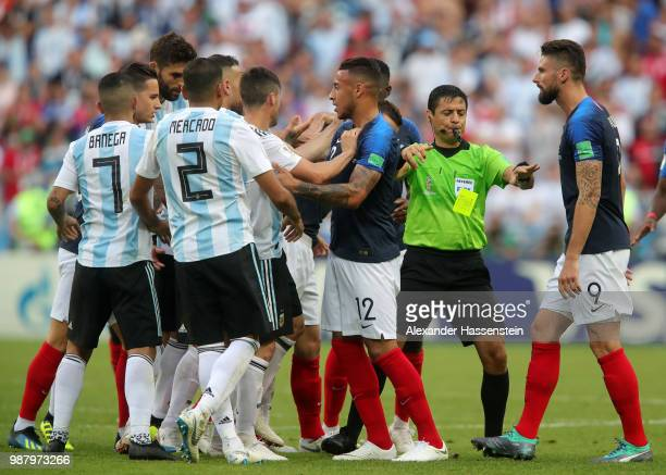 Match referee Alireza Faghani separates players as Corentin Tolisso of France confronts Argentina players during the 2018 FIFA World Cup Russia Round...