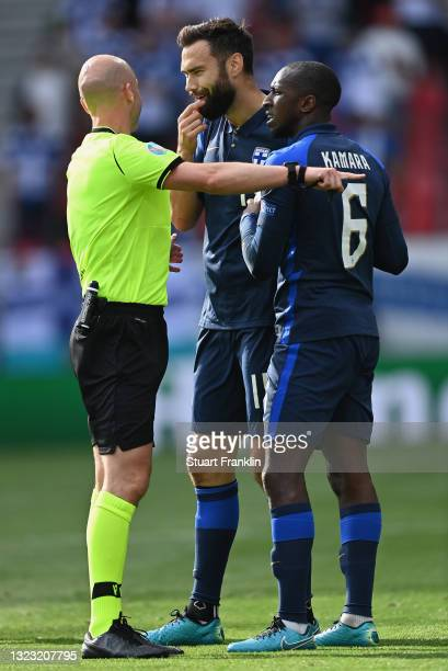 Match Referee, Anthony Taylor speaks with Tim Sparv and Glen Kamara of Finland during the UEFA Euro 2020 Championship Group B match between Denmark...
