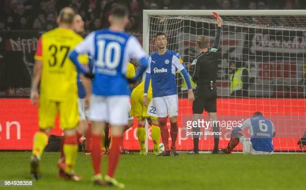 Match referee Arne Aarnink showing Kiel's David Kinsombi the red card during the German 2nd division Bundesliga soccer match between Holstein Kiel...