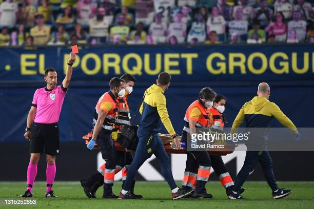 Match referee Artur Dias shows a red card to Etienne Capoue of Villarreal as he is stretchered off during the UEFA Europa League Semi-final First Leg...