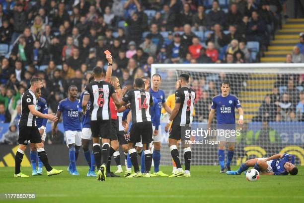 Match referee Craig Pawson shows a red card to Isaac Hayden of Newcastle United during the Premier League match between Leicester City and Newcastle...