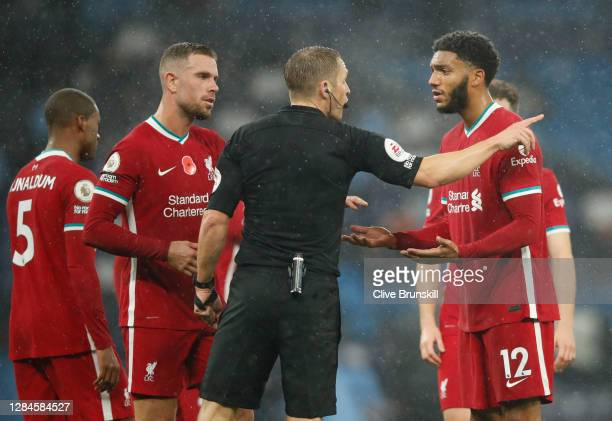 Match referee Craig Pawson speaks with Joe Gomez of Liverpool after a penalty is given during the Premier League match between Manchester City and...