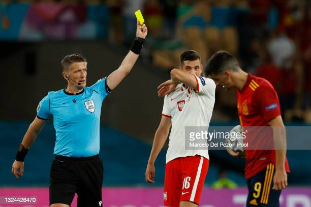 Match Referee, Daniele Orsato shows a yellow card to Kamil Jozwiak of Poland during the UEFA Euro 2020 Championship Group E match between Spain and...
