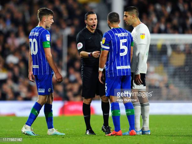 Match Referee Dean Whitestone speaks with Sam Sayed Morsy of Wigan Athletic during the Sky Bet Championship match between Fulham and Wigan Athletic...