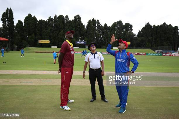 Match referee Dev Govindjee and Jason Holder of The West Indies look on as Rashid Khan Arman of Afghanistan tosses the coin before the Afghanistan v...