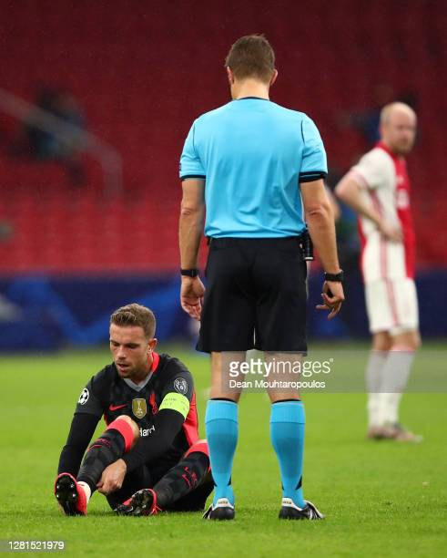Match referee Felix Brych waits as Jordan Henderson of Liverpool adjusts his sock tape during the UEFA Champions League Group D stage match between...