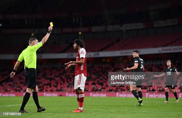 Match referee Graham Scott shows a yellow card to Mohamed Elneny of Arsenal during the Premier League match between Arsenal and Burnley at Emirates...