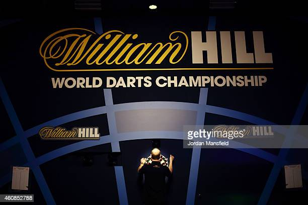 A match referee hangs the dartboard ahead of Day Seven of the William Hill PDC World Darts Championships at Alexandra Palace on December 27 2014 in...