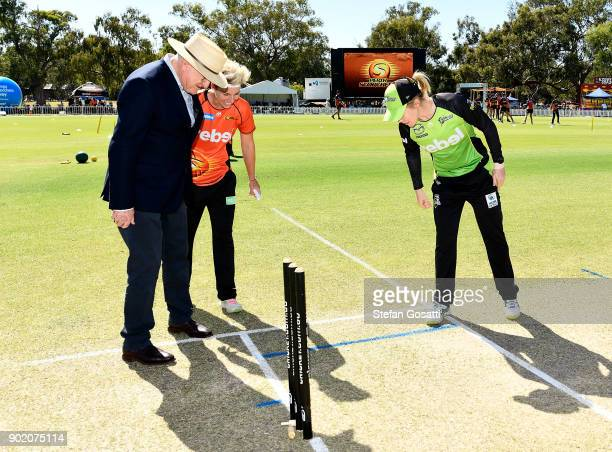 Match referee Ian Thomas Elyse Villani of the Scorchers and Alex Blackwell of the Thunder look to see the result of the coin toss before the Women's...