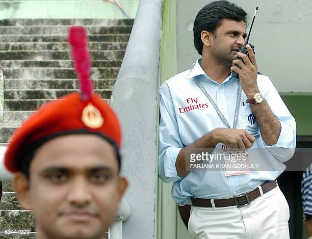 Match referee Javagal Srinath talks over a walkietalkie after inspecting the pitch after rains subsided as the second Test match between Bangladesh...