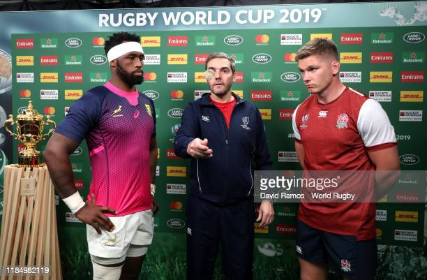 Match referee Jerome Garces flips the coin as Siya Kolisi of South Africa and Owen Farrell of England watches during the coin toss prior to the Rugby...