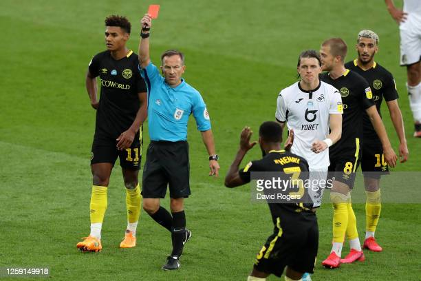 Match referee Keith Stroud shows a red card to Rico Henry of Brentford during the Sky Bet Championship Play Off Semifinal 1st Leg match between...