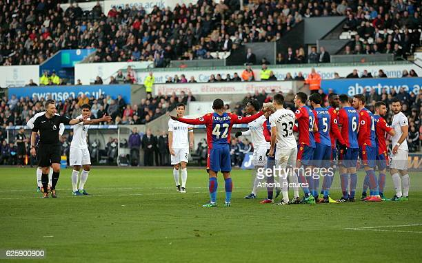 Match referee Kevin Friend attempts to calm things down at the wall before a free kick taken by Gylfi Sigurdsson of Swansea City which equalised to...