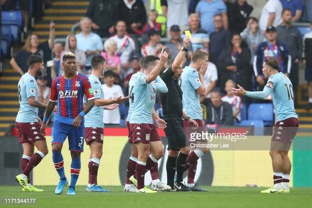 Match referee Kevin Friend gives a yellow card to Jack Grealish of Aston Villa during the Premier League match between Crystal Palace and Aston Villa...
