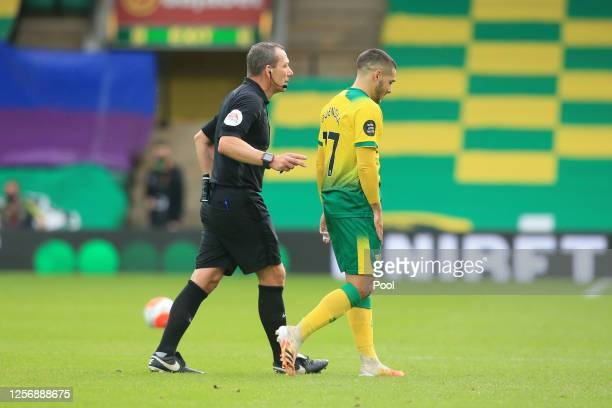 Match Referee, Kevin Friend walks Emiliano Buendia of Norwich City off the pitch following being shown a red card after a VAR check for violent...